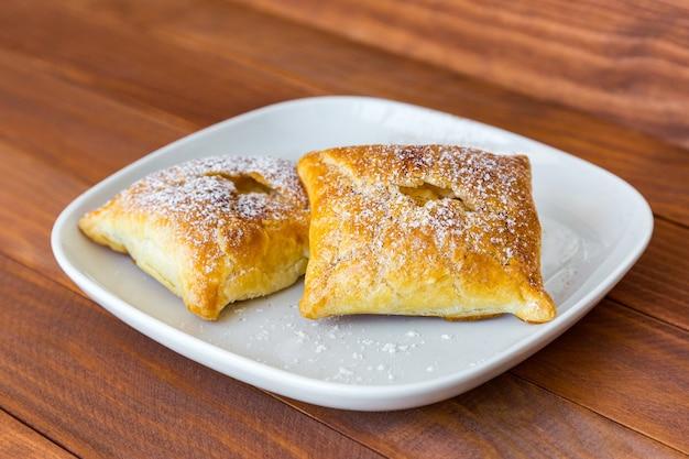 Świeżo upieczone słodkie bułeczki posypane cukrem pudrem i cynamonem na białym talerzu na drewnianym stole.