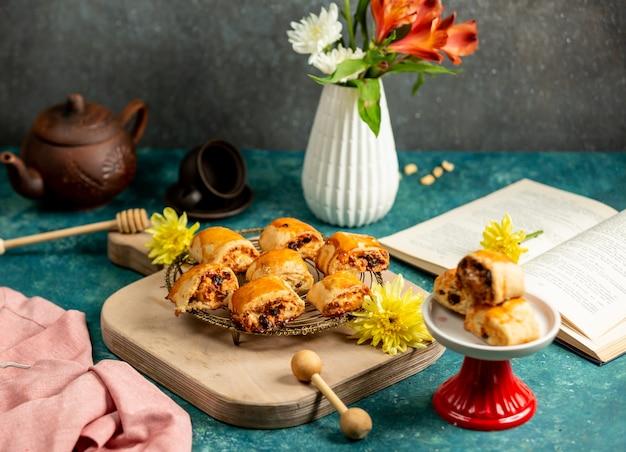 Świeżo upieczone słodycze, otwarta książka kucharska i kwiaty