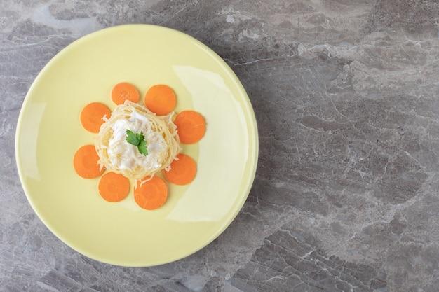 Świeżo upieczone spaghetti z marchewką na talerzu, na marmurze. wysokiej jakości zdjęcie
