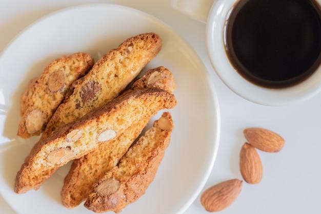 Świeżo upieczone włoskie cantucci z migdałami i filiżanką kawy