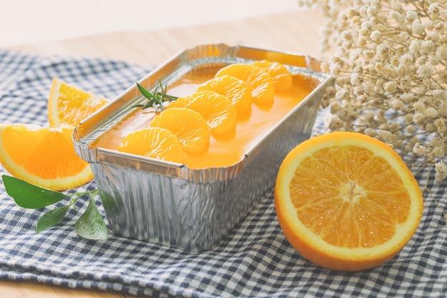 Świeżo upieczony biszkopt mandarynkowy udekorowany pomarańczowym sosem galaretkowym i pomarańczowym miąższem w bochenku z folii aluminiowej.