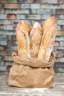 Świeżo upieczony bochenek chleba rustykalnego w papierowych torebkach