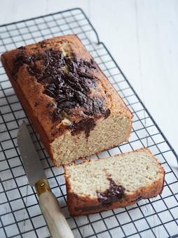 Świeżo upieczony chleb bananowy na stojaku chłodzącym z czekoladą na wierzchu