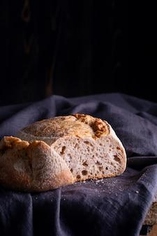 Świeżo upieczony chleb domowej roboty z ciasta kwaśnego na ciemnej lnianej serwetce, drewniany stół.