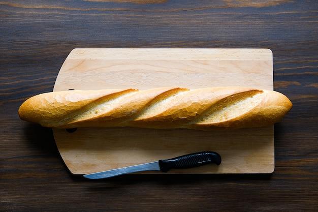 Świeżo upieczony chleb, nóż kuchenny z czarnym plastikowym uchwytem, deska do krojenia na drewnianym stole.