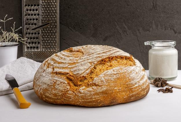 Świeżo upieczony chleb rzemieślniczy na zakwasie z zakwasem na blacie kuchennym