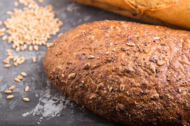 Świeżo upieczony chleb z ziarnami na czarnej betonowej powierzchni. widok z boku, selektywne focus.