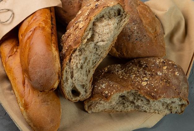 Świeżo upieczony domowy chleb, całe i połamane kawałki. chleb leży na tkaninie.