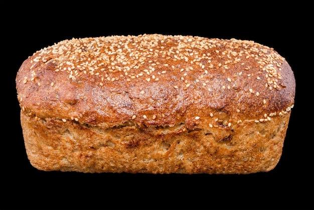 Świeżo upieczony domowy chleb na czarnym tle, chleb żytni z czerwonymi jagodami i sezamem