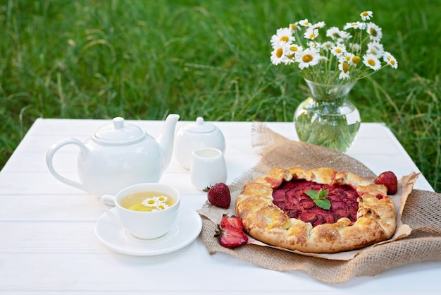Świeżo upieczony domowy galette lub otwarte ciasto truskawkowe, filiżanka herbaty ziołowej, czajnik i wazon z bukietem kwiatów stokrotki.
