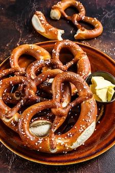 Świeżo upieczony domowy precel z solą na rustykalnym talerzu