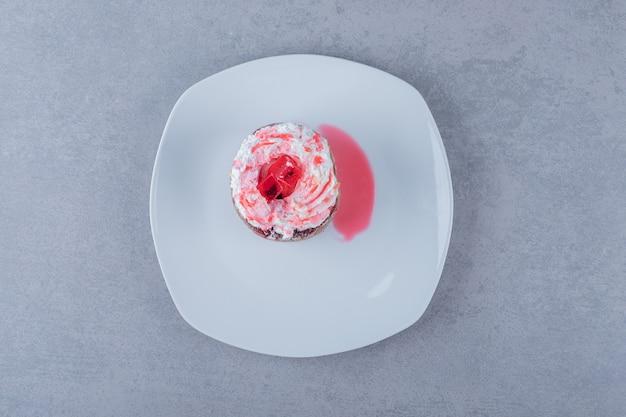 Świeżo upieczony kremowy muffin na białym talerzu