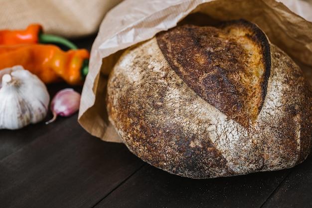 Świeżo upieczony okrągły bochenek chleba na zakwasie na drewnianym stole z warzywami. rzemieślniczy chleb na zakwasie.
