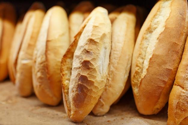 Świeżo upieczony pachnący i chrupiący chleb z piekarni leży i jest przechowywany na blacie na sprzedaż