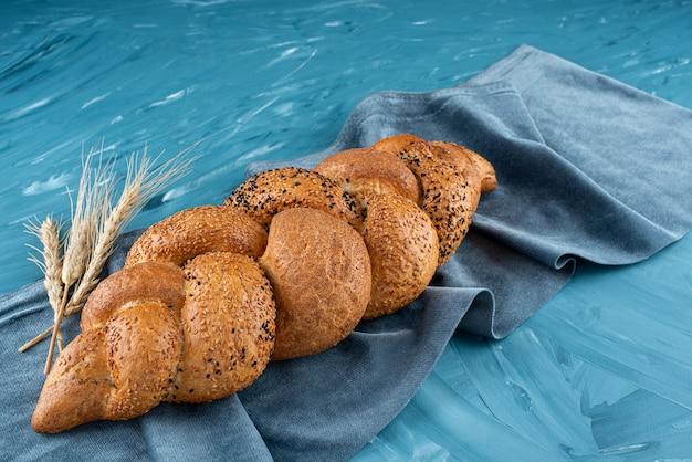 Świeżo upieczony pleciony bochenek chleba na ciemnym obrusie.