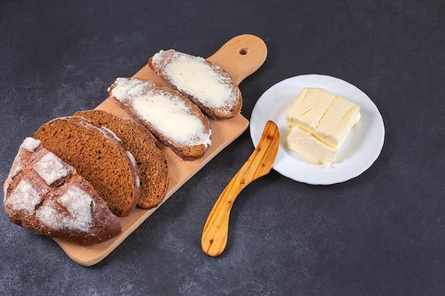Świeżo upieczony pokrojony chleb rzemieślniczy z masłem na drewnianej desce do krojenia