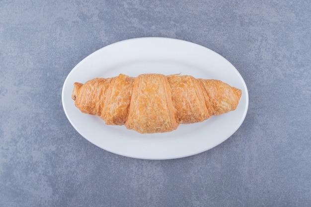 Świeżo upieczony rogalik francuski na białym talerzu na szarym tle.