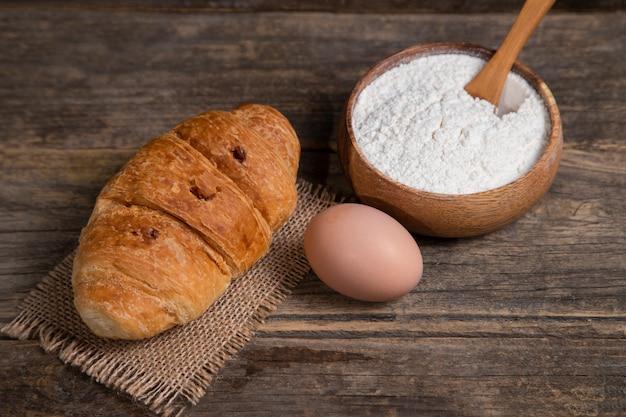 Świeżo upieczony rogalik z brązowym jajkiem kurzego i mąką ułożony na drewnianym stole. wysokiej jakości zdjęcie