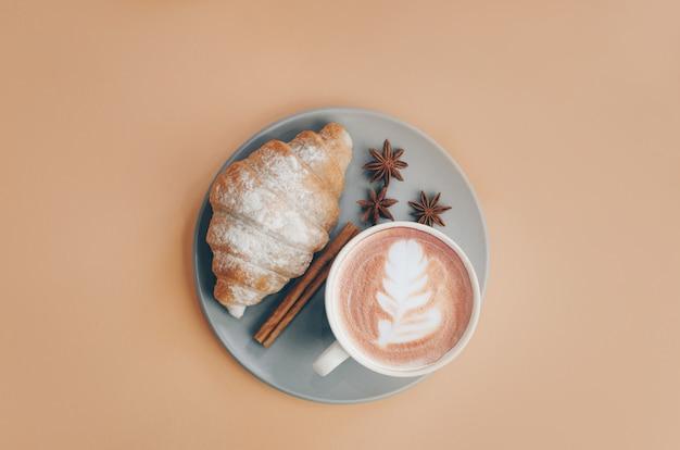 Świeżo upieczony rogalik z filiżanką kawy i latte art, cynamonem i anyżem. leżał płasko