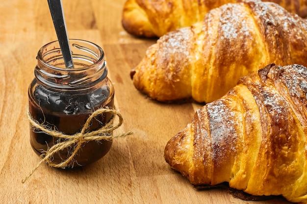 Świeżo upieczony rogalik z konfiturą jagodową w słoiku na drewnianym biurku. koncepcja francuskiego śniadania. domowe ciasto.