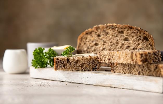Świeżo upieczony rzemieślniczy chleb wieloziarnisty z masłem i pasztetem