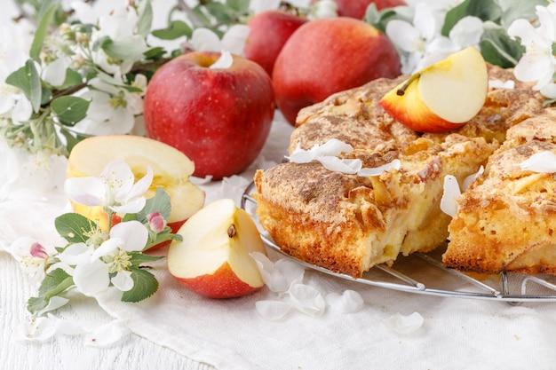 Świeżo upieczony szarlotka na stole z jabłkami, kawałek w talerzu