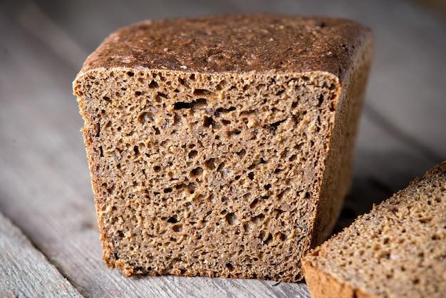 Świeżo upieczony zdrowy chleb na starym drewnianym tle. chleb pełnoziarnisty.
