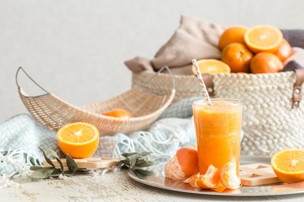Świeżo uprawiany ekologiczny świeży sok pomarańczowy we wnętrzu domu, turkusowy koc i kosz owoców. zdrowe jedzenie. witamina c