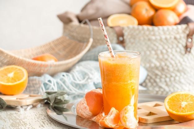Świeżo uprawiany ekologiczny świeży sok pomarańczowy we wnętrzu domu, turkusowy koc i kosz owoców