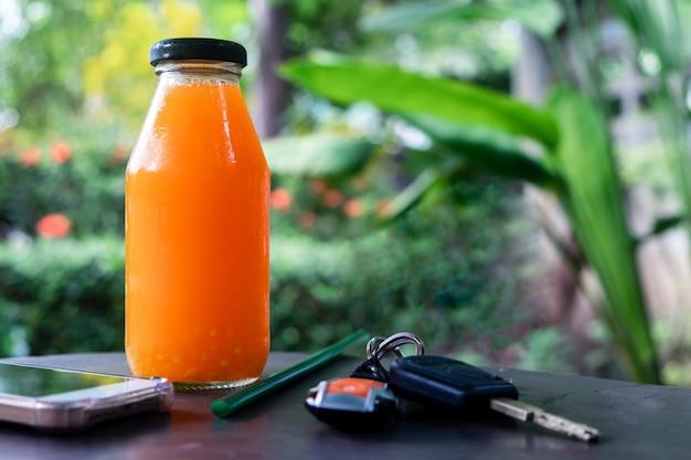 Świeżo wyciskany sok pomarańczowy w butelce ze smartfonem i kluczami