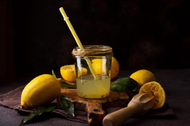 Świeżo wyciskany sok z połówek cytryny z sokowirówką w szklanym słoju, selektywna ostrość
