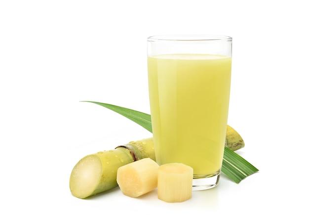 Świeżo wyciskany sok z trzciny cukrowej ze świeżej trzciny cukrowej w plasterkach na białym tle.