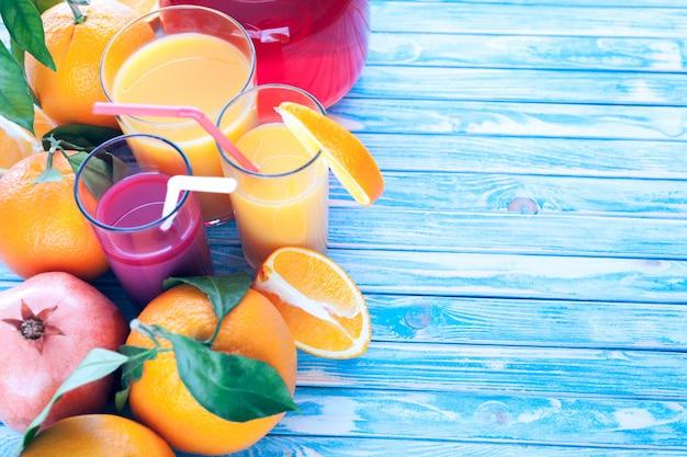 Świeżo wyciśnięte soki pomarańczowe i granatowe z pomarańczami i owocami granatu