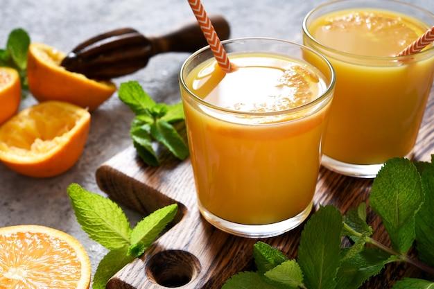 Świeżo wyciśnięty sok pomarańczowy na szarym tle betonu z miętą.