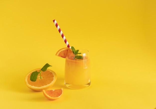 Świeżo wyciśnięty sok pomarańczowy z kawałkami żółto-czerwonej pomarańczy i liśćmi młodej mięty. kartonowa tubka do picia. żółte tło. koncepcja zdrowego odżywiania. zapobieganie chorobom za pomocą witaminy c. skopiuj przestrzeń