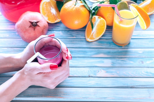 Świeżo wyciśnięty sok z granatów w rękach kobiet z pomarańczami i owocami granatu