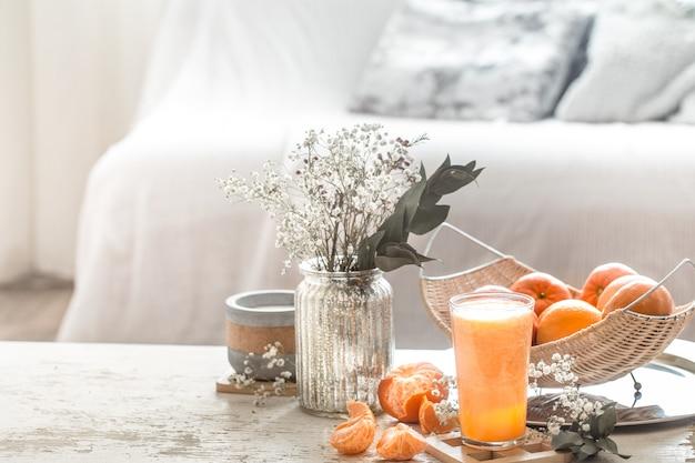 Świeżo wyhodowany organiczny świeży sok pomarańczowy we wnętrzu domu, z turkusowym kocem i koszem owoców