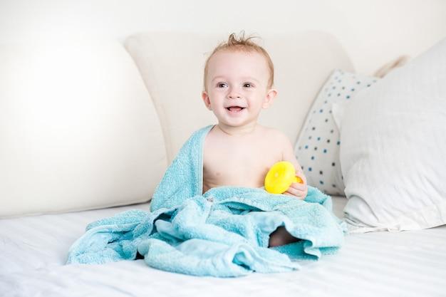 Świeżo wykąpany chłopczyk przykryty niebieskim ręcznikiem siedzący na dużej sofie