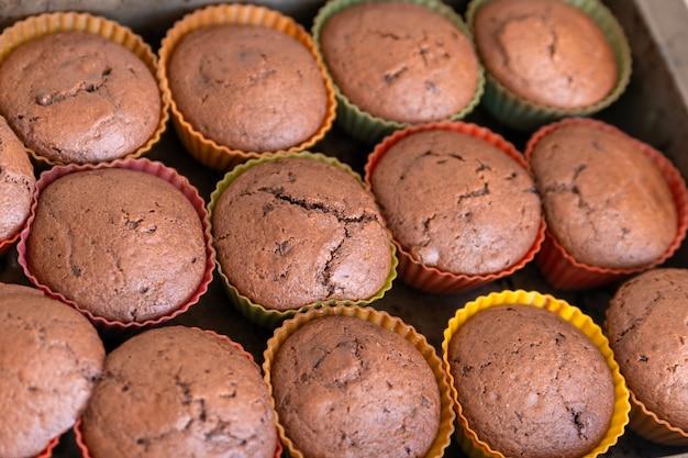 Świeżo wykonane babeczki czekoladowe na blasze do pieczenia. domowe wypieki. zbliżenie.