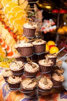 Świeżo wykonane czekoladowe babeczki, ozdobione kremem i kulkami, stoją na stojaku. wakacyjna atmosfera, przepyszny deser. batonik.