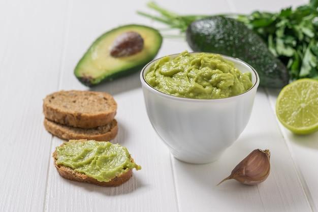 Świeżo wykonane guacamole w białej filiżance i na kromkach chleba. dieta wegetariańska meksykańskie jedzenie awokado. surowe jedzenie.