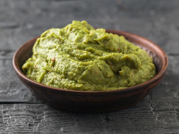 Świeżo wykonane guacamole w glinianej misce na ciemnym rustykalnym stole. surowe jedzenie.
