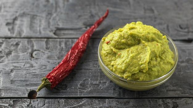 Świeżo wykonane guacamole w misce i papryczka chili na ciemnym rustykalnym stole.
