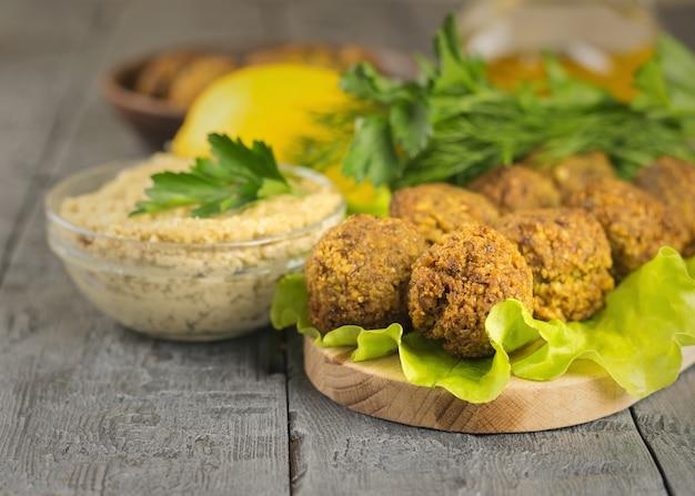Świeżo wykonany falafel na desce do krojenia z sosem tahina, ziołami i cytryną