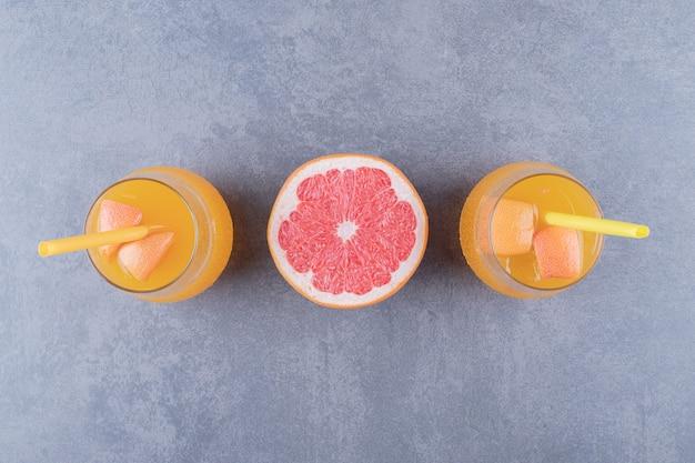 Świeżo wykonany sok pomarańczowy z dojrzałych grejpfrutów na szarym tle.