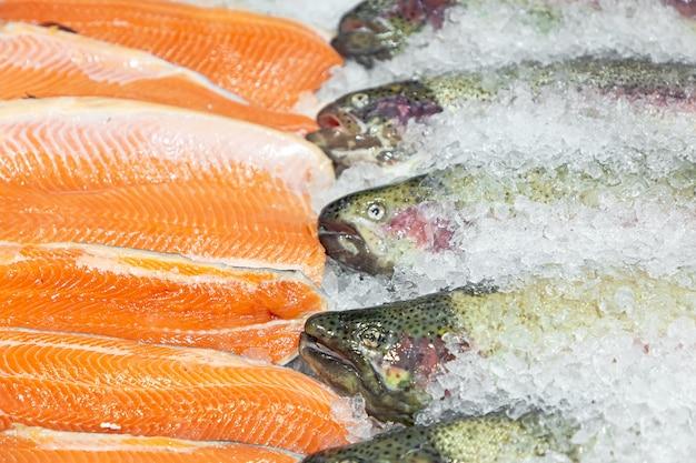Świeżo wypatroszone duże czerwone ryby z pstrąga i filety z łososia leżą na blacie w pokruszonym lodzie.