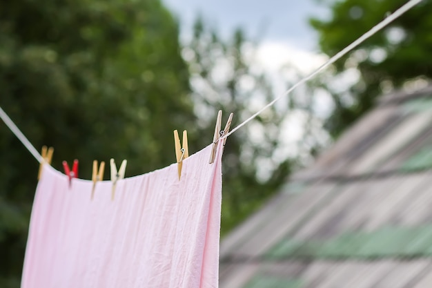 Świeżo wyprana pościel wisząca na linie na zewnątrz. suszenie ubrań na wiejskim podwórku.