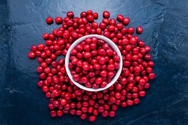 Świeżo zebrana wiśnia z kroplami rosy i wody w białej misce. pojęcie zbiorów.