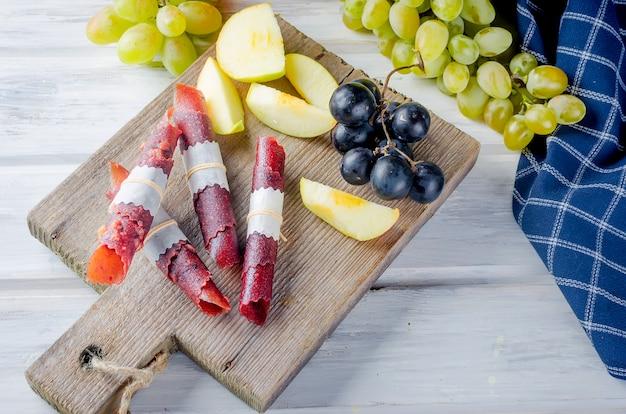 Świeżo zebrane jabłka, winogrona i owoce pastylki na ciemnej powierzchni