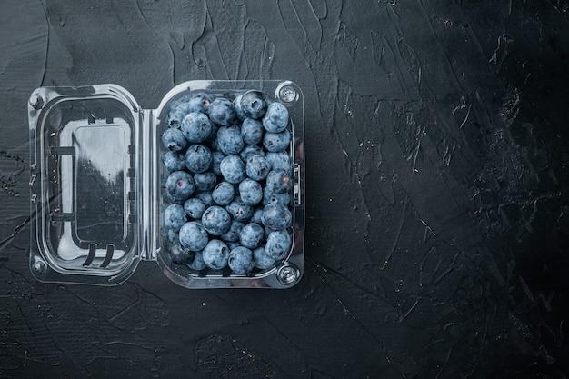 Świeżo zebrane jagody, na tacy, na czarnym stole, widok z góry na płasko